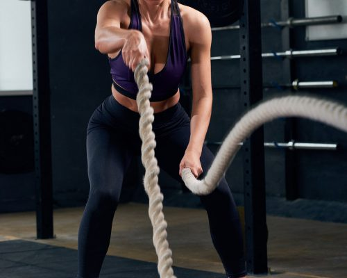 young-woman-training-with-ropes-in-crossfit-gym-22GZ5B5-min.jpg